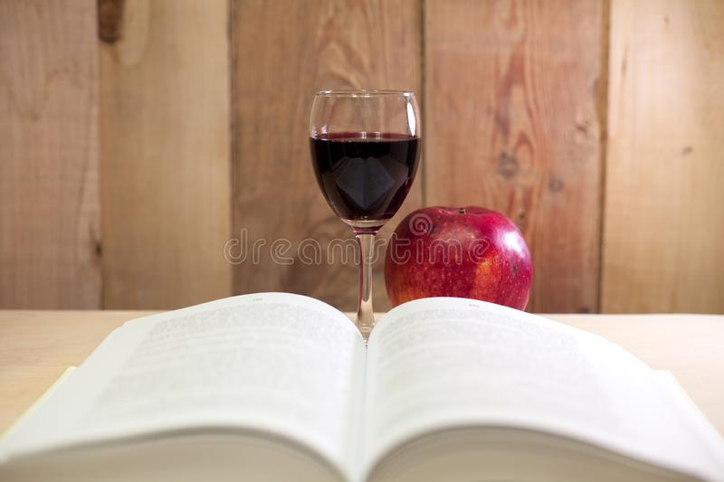 Glass of red wine with an apple and a book stock photography