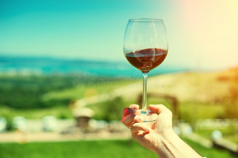 A glass with red wine on a background of a mountain landscape. And the sea stock photos