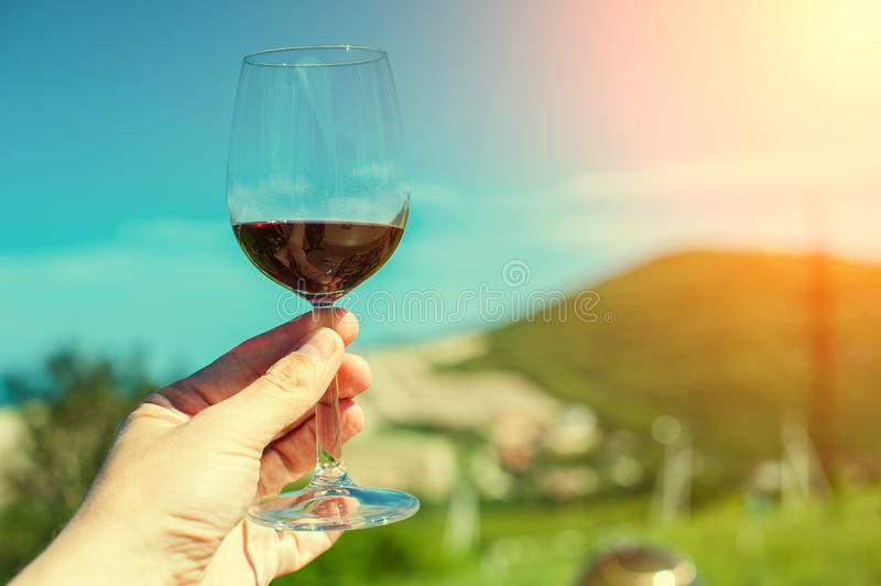 A glass with red wine on a background of a mountain landscape in the sun. A glass with red wine on a background of a mountain landscape and the sea in the sun stock image