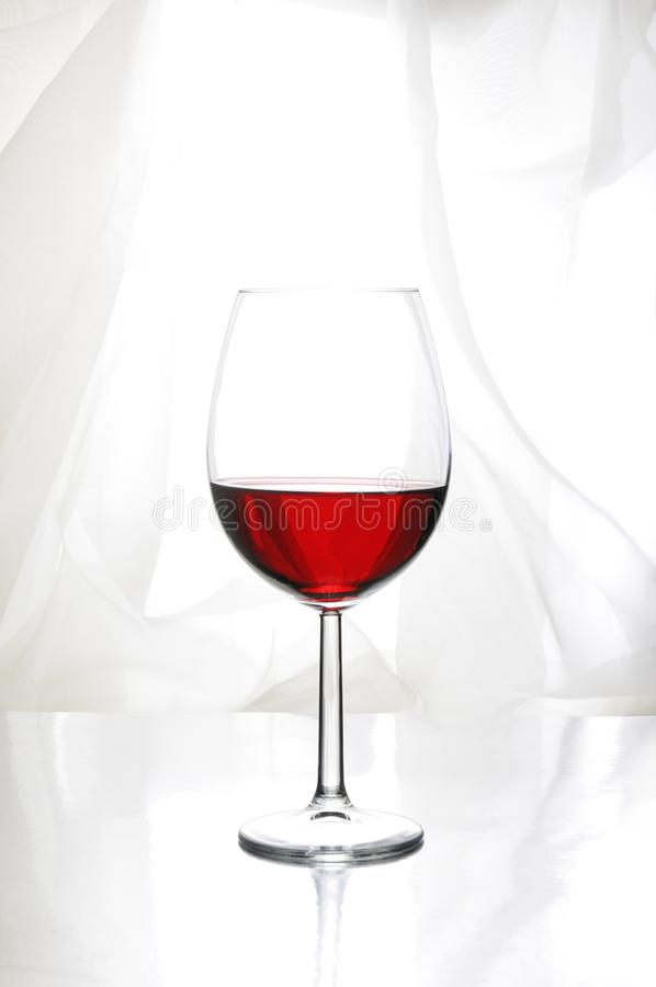 A glass of red wine. In Bordeaux-shaped glass on a light background royalty free stock photo
