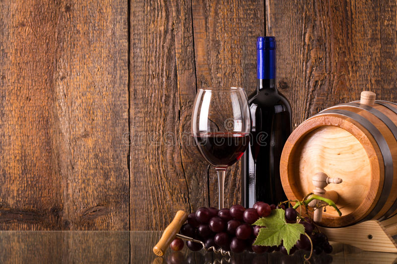 Glass of red wine with bottle barrel grapes and wooden background stock photography