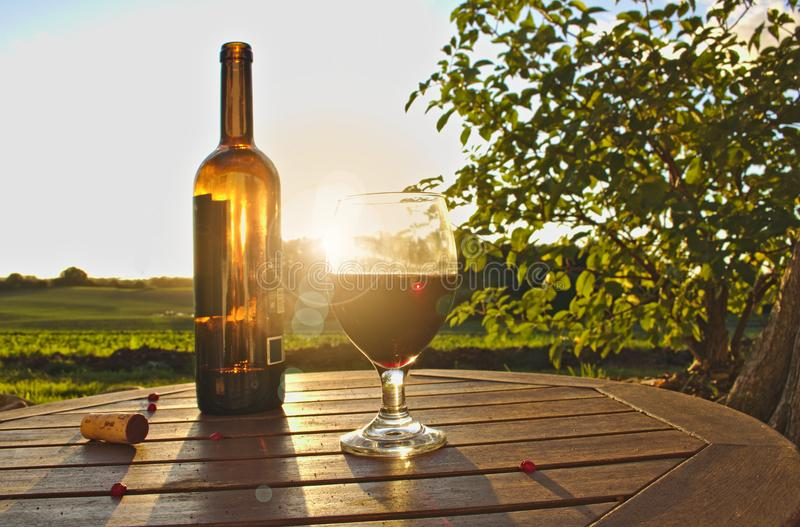 Glass of red wine with bottle, cork and red berries on wooden table with green fields, bush and sunset in the background stock photos