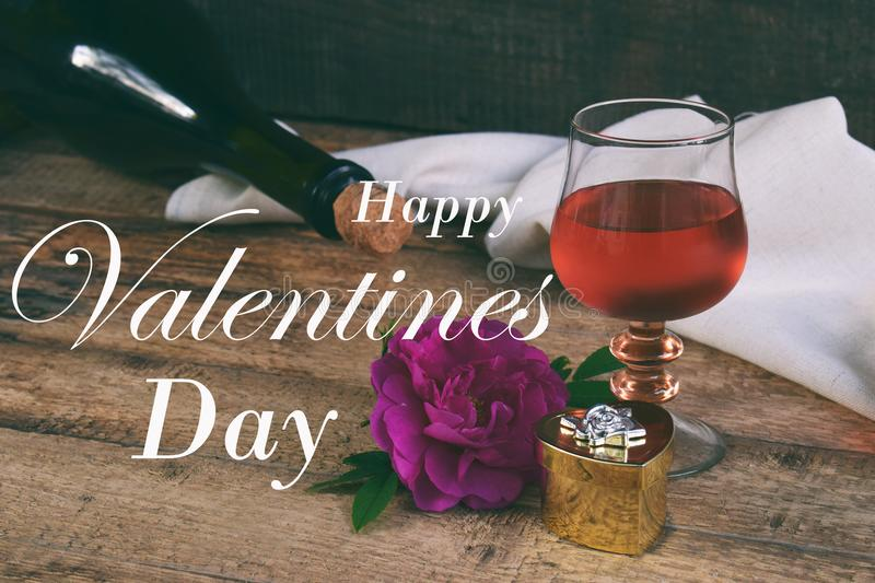 A glass of red wine, bottle and rose on rustic wood table. Valentine`s day still life. Concept greeting card with the inscription royalty free stock photography