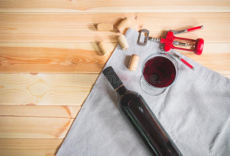 Glass of red wine, bottle of wine, wine corks and corkscrew stock photography