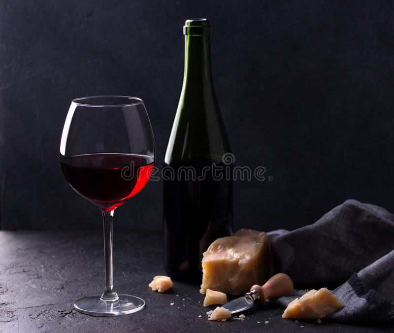 Glass of red wine, cheeses and cheese knife on black background stock photography