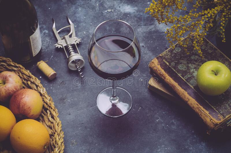 A glass of red wine on a dark background. Wine on the table, with fruits, a bottle and old books. Relax and romance concept.  stock photos