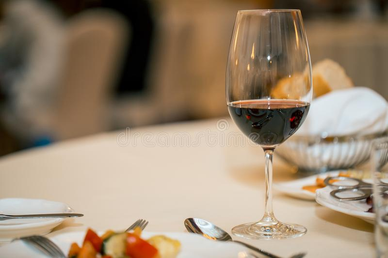 Glass of red wine and dinner on a set table. a restaurant. waiting for the meeting. Glass of red wine and dinner on a set table. a restaurant. Copy space stock image