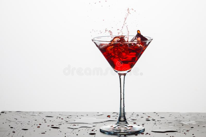 Glass of Red Wine With Drops Against White Background. stock photo