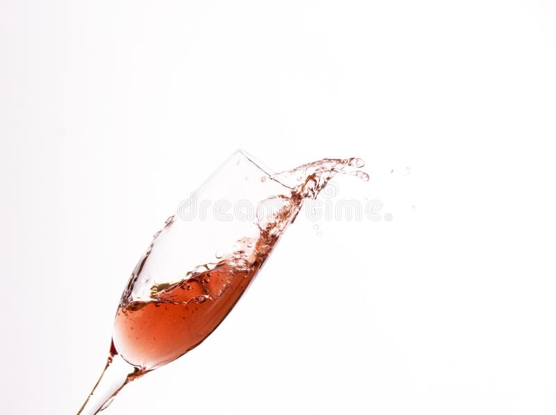 A glass of red wine in splashing motion stock photography