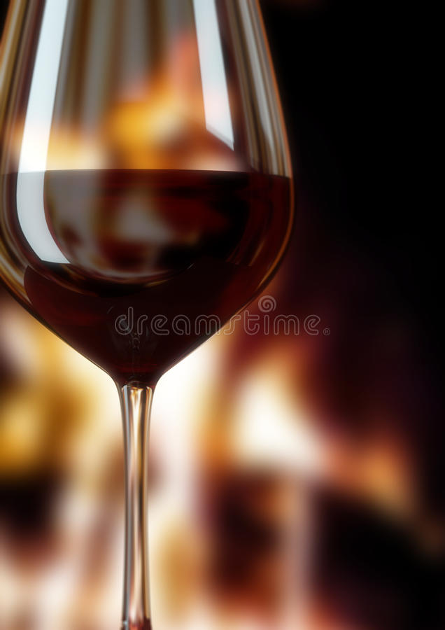 Glass of red wine and fire place stock image