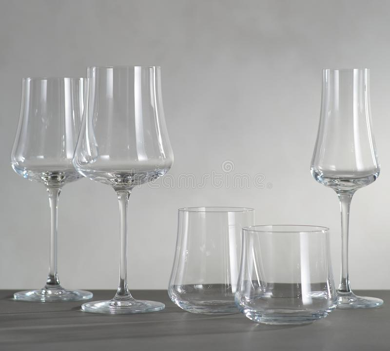 A glass of red wine and four empty wine glasses stock photo