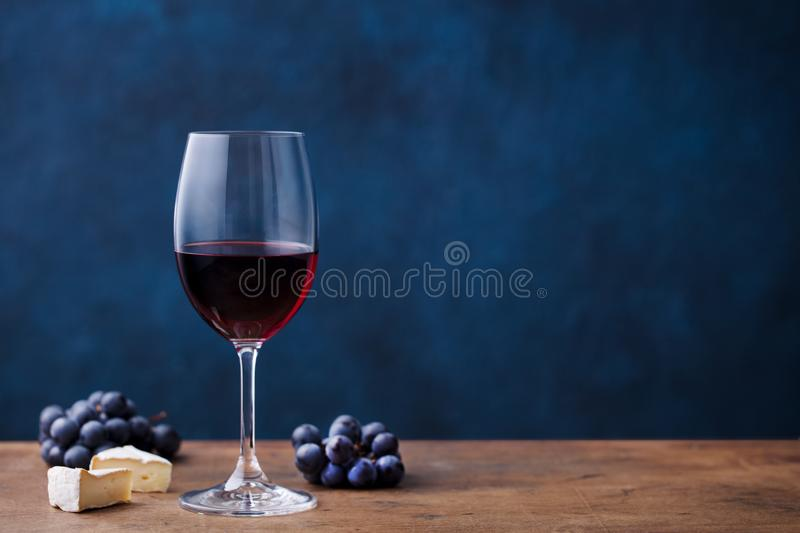 Glass of red wine with fresh grape and cheese on wooden table. Blue background. Copy space. stock image