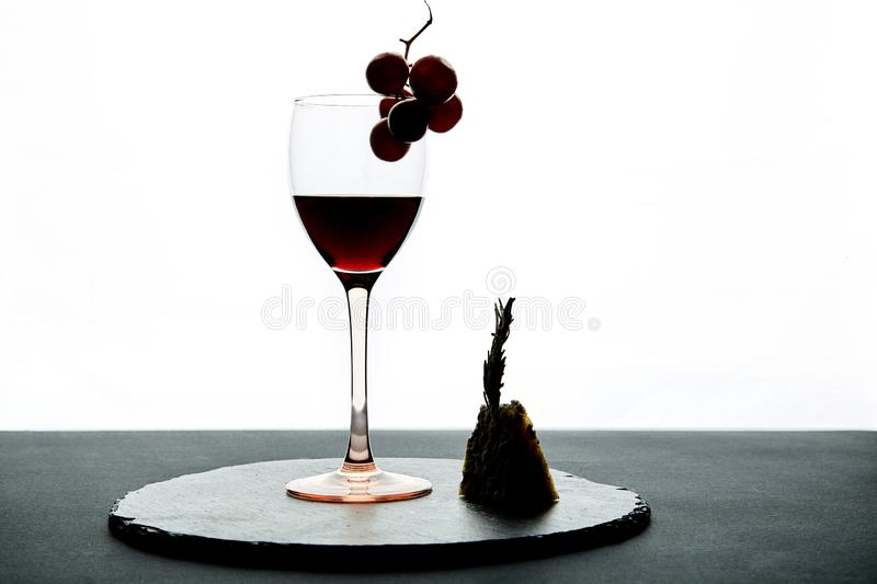 Glass of red wine garnished with grape and piece of hard cheese.  royalty free stock images