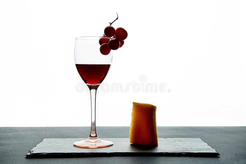 Glass of red wine garnished with grape and piece of hard cheese.  stock photography