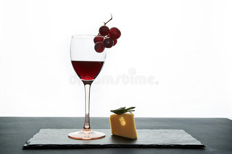 Glass of red wine garnished with grape and piece of savory hard cheese on slate dish.  royalty free stock photography