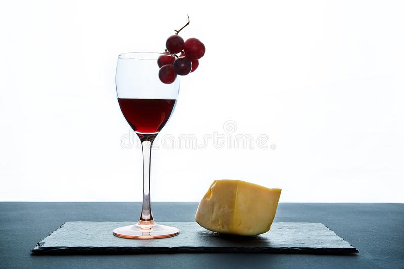 Glass of red wine garnished with grape and piece of savory hard cheese on slate dish.  stock images
