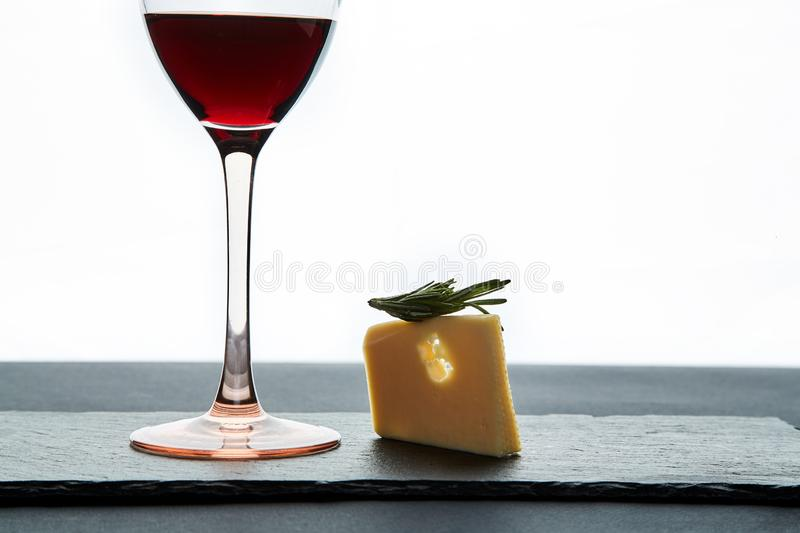 Glass of red wine garnished with grape and piece of savory hard cheese on slate dish.  royalty free stock photo