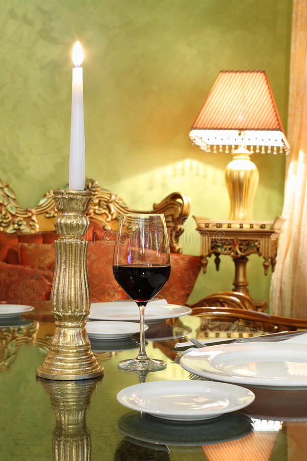 Glass with red wine and gold candlestick