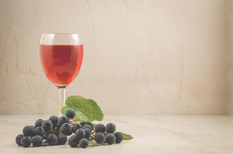 Glass of red wine and grape over white/glass of red wine and grape on a white marble. Selective focus. Glass of red wine and grape over white/glass of red wine stock photo