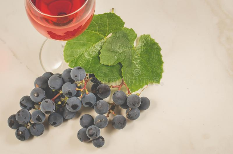 Glass of red wine and grape/glass of red wine and grape on a white marble. Top view royalty free stock photography