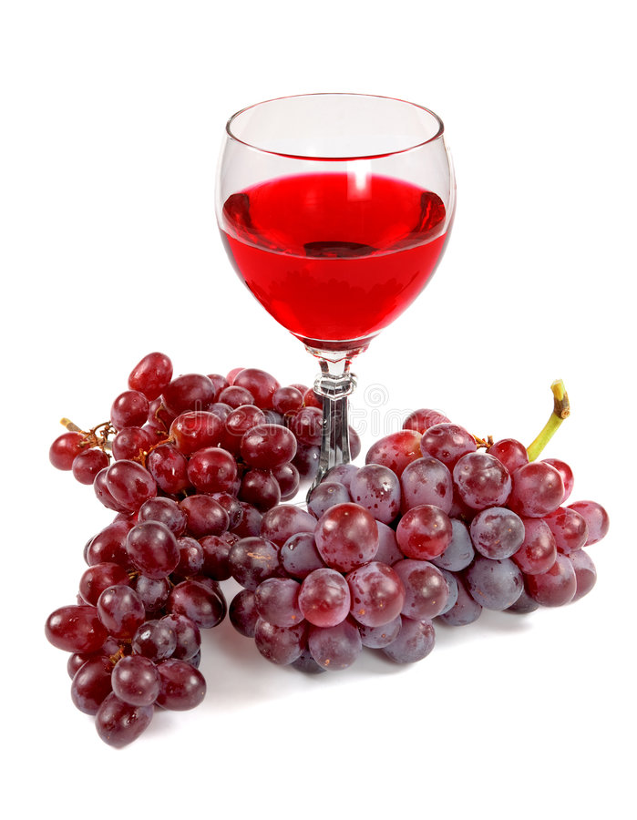 Glass of red wine and grapes clusters. On a white background royalty free stock photography