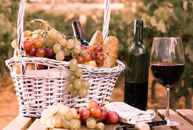 Glass of red wine grapes and picnic basket on table in field. Still life with glass of red wine grapes and picnic basket on table in field stock photos