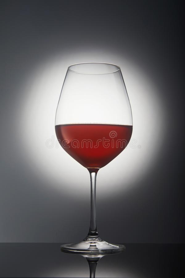 Glass with red wine on a gray background with backlight and reflection. Drink, alcohol, white, wineglass, beverage, liquid, isolated, winery, cabernet, merlot royalty free stock image