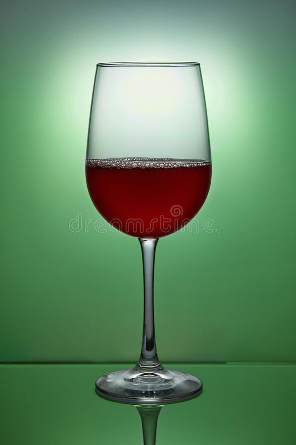 Glass of red wine on green royalty free stock images