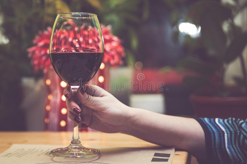 Glass of red wine in the hand of a girl stock photography