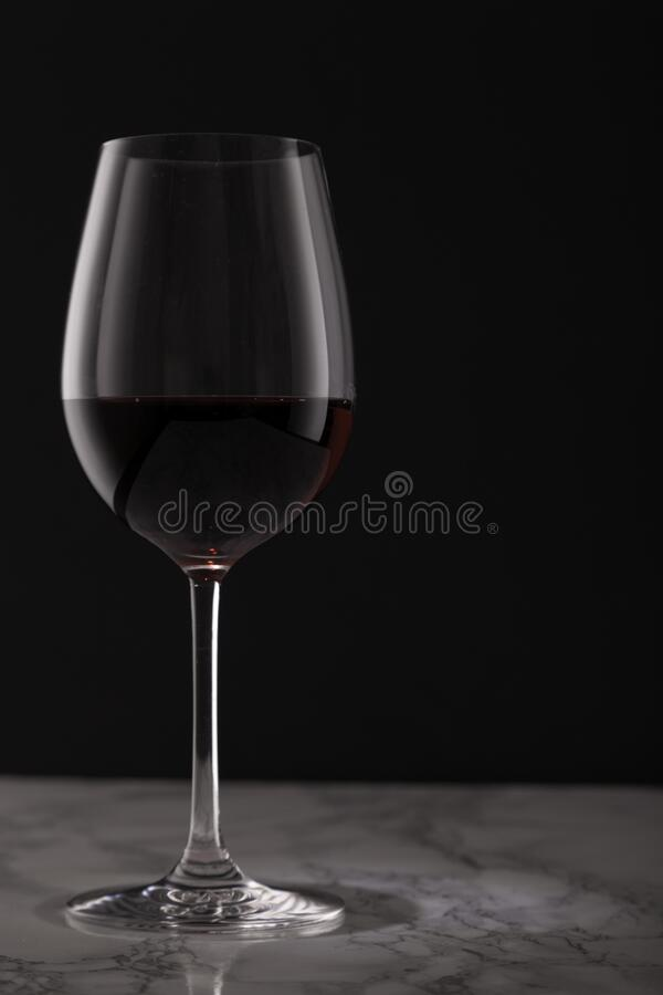 Glass of red wine on marble table royalty free stock photos