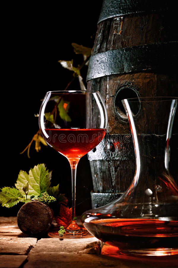 A glass of red wine next to a decanter stock image