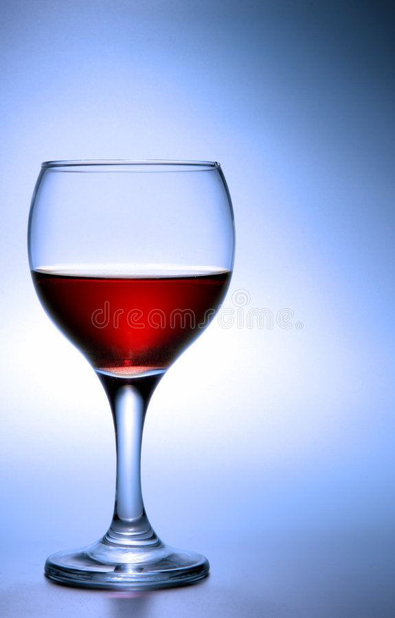 Glass of red wine over blue royalty free stock photos