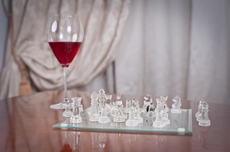 Glass with red wine and pieces on the chessboard. Set of chess figures on the playing board near a glass with red win. Glass chess royalty free stock images