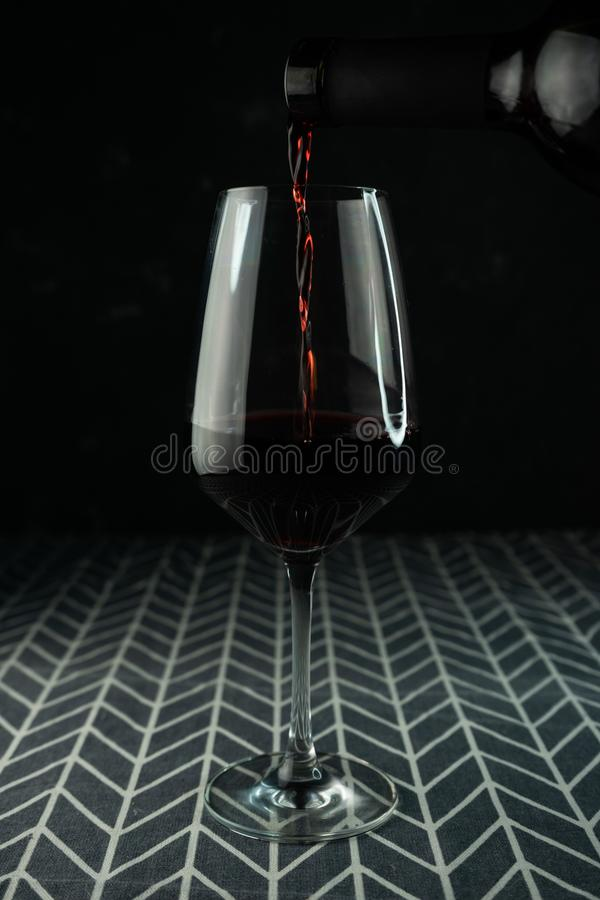 a glass of red wine with a pouring drink royalty free stock image