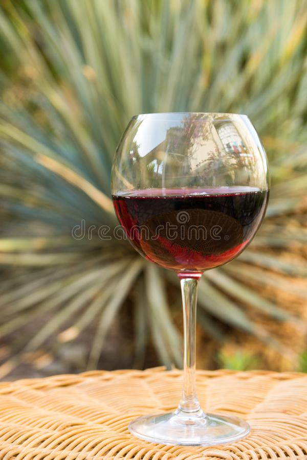 Glass of Red Wine on Rattan Wicker Table in Garden on Villa Mansion. Cozy summer early fall evening. Authentic Lifestyle Image. Relaxation Indulgence Gourmet royalty free stock photography