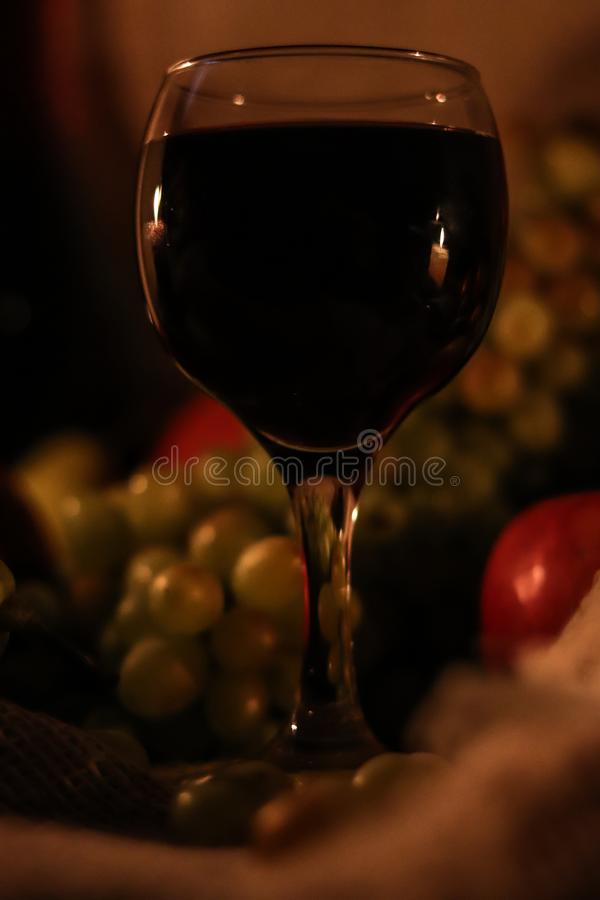 Glass of red wine with reflection of two candles flames on it close up and fruits: grapes, apple on sackcloth background royalty free stock image