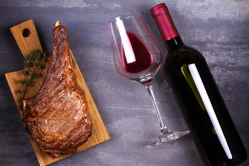 Glass of red wine and rib eye beef steak royalty free stock images