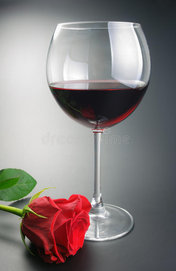 Glass of red wine and rose flower. Glass of red wine and red rose flower arranged on neutral gradient background stock photography