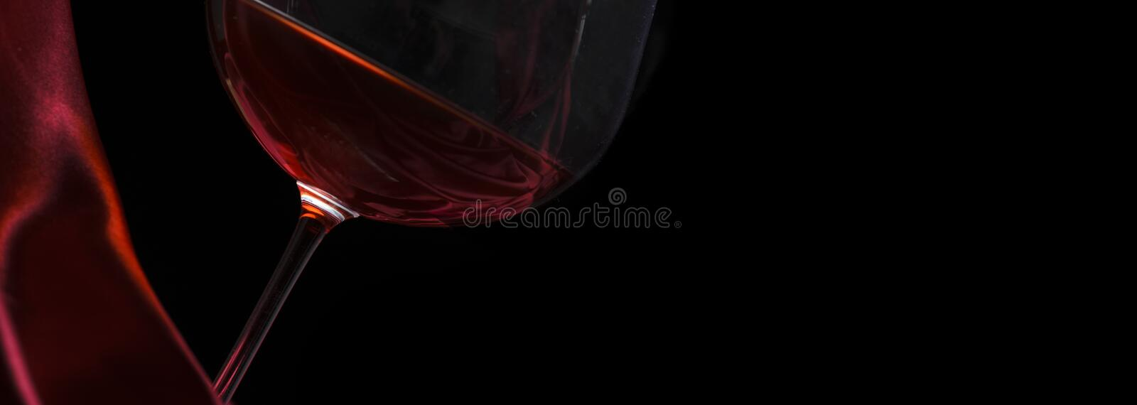 Glass of red wine on red silk against black background. Wine list design background stock image