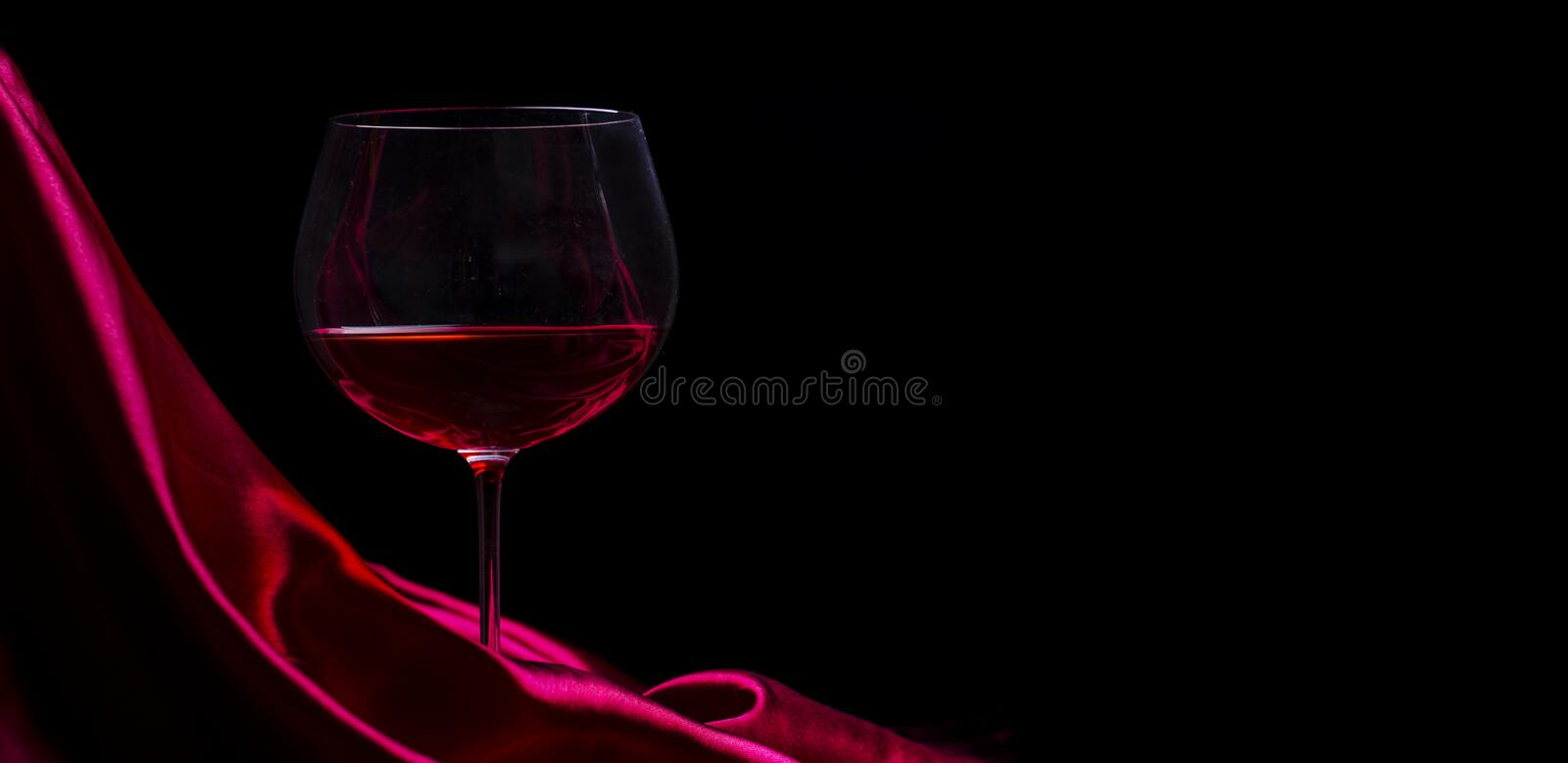 Glass of red wine on red silk against black background. Wine list design background royalty free stock image