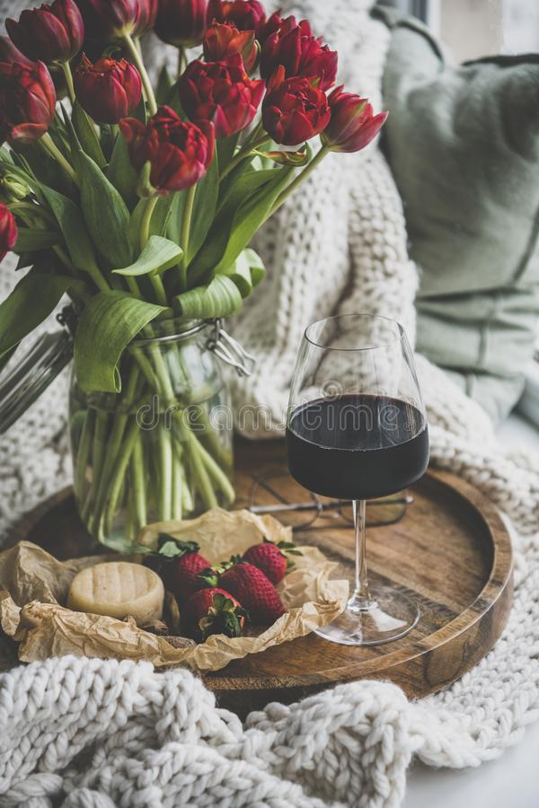 Glass of red wine, snacks and spring red tulips royalty free stock photo