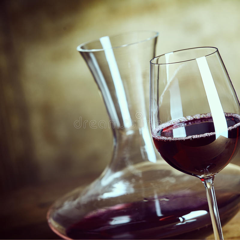 Glass of red wine with a stylish decanter royalty free stock photography