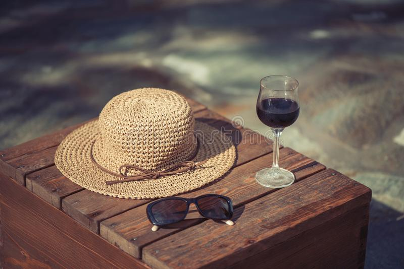 Glass of red wine Sunglasses and thatch hat on the wooden table. On susnet royalty free stock photography