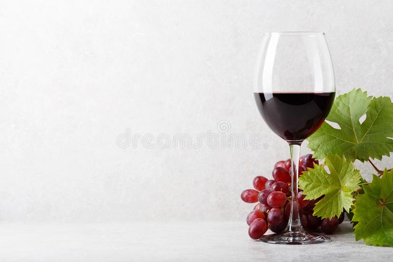 A glass of red wine on the table, grapes and grape leaves. Light background royalty free stock photography