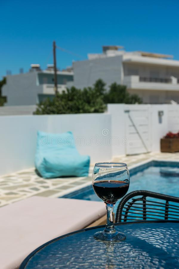 A glass of red wine on the table by the pool. Relax in the hotel on a sunny day stock photo