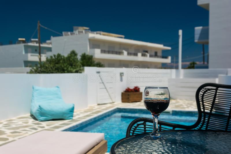 A glass of red wine on the table by the pool. Relax in the hotel on a sunny day stock photography