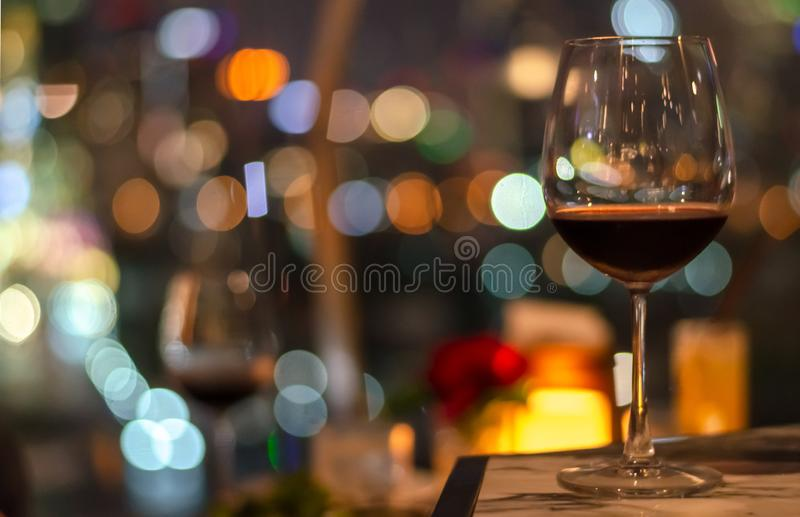 A glass of red wine on table of rooftop bar. With colorful bokeh of city light and space for text stock photography