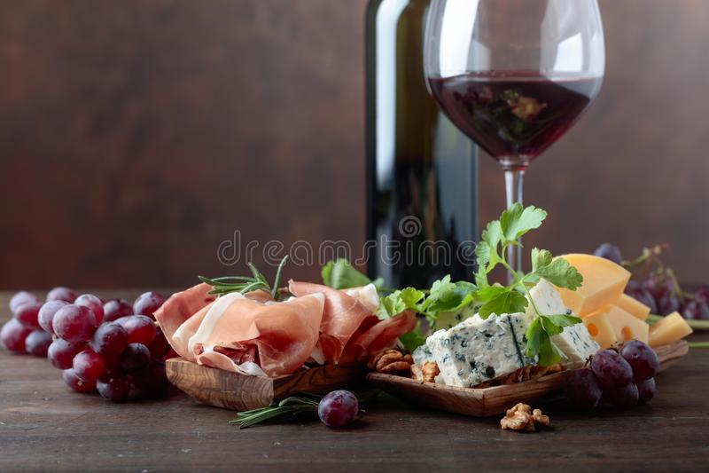 Glass of red wine with various cheeses , fruits and prosciutto . stock images