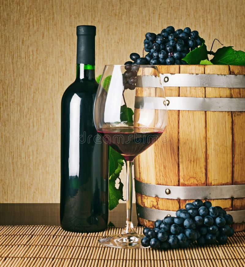 Glass of red wine, wine bottle and wooden barrel. Glass of red wine, wine bottle, wooden barrel and bunches of ripe grape on table. Winemaking product. Classical stock images