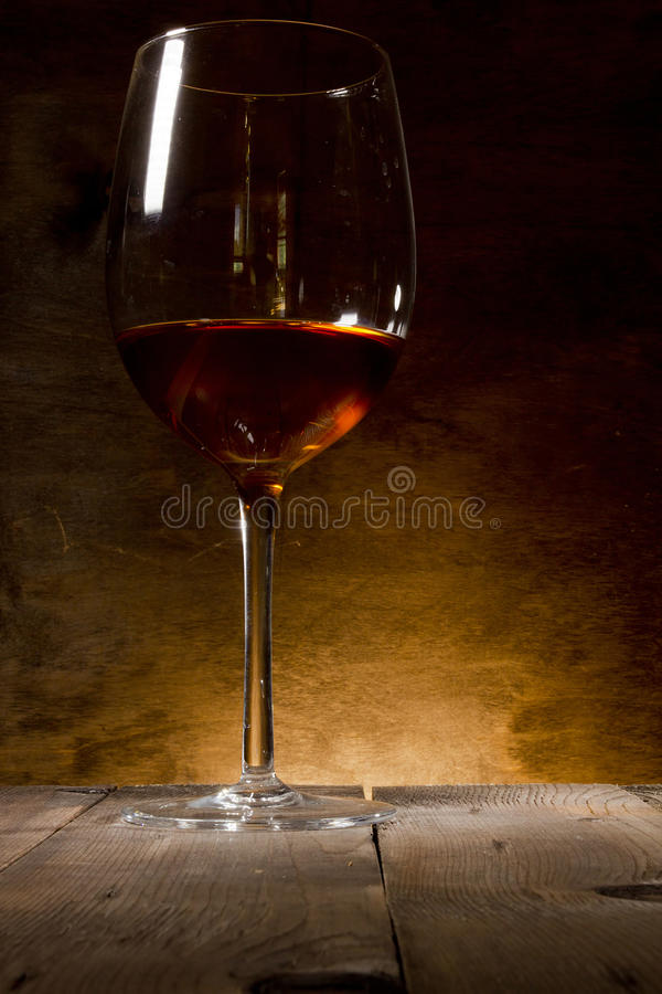 Glass of red wine. On a wooden background stock photo